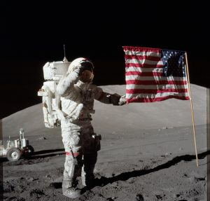 Astronaut Eugene A. Cernan, Apollo 17 commander, is photographed next to the deployed United States flag during lunar surface